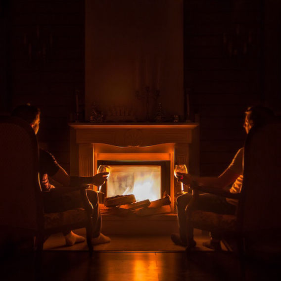 two people seated facing fireplace with wine glasses in hand