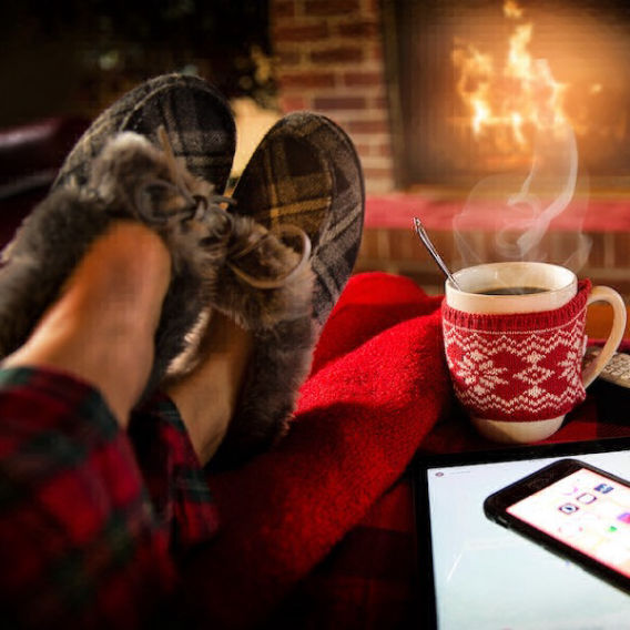 feet propped up in slippers with coffee on table in front of fire