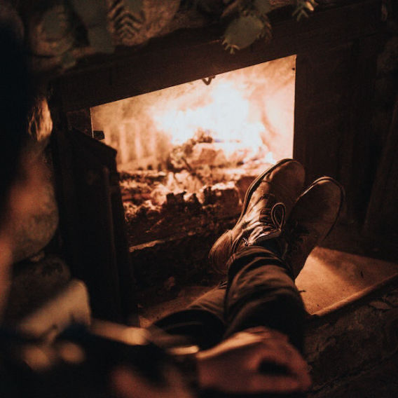 person warming boots in front of fireplace